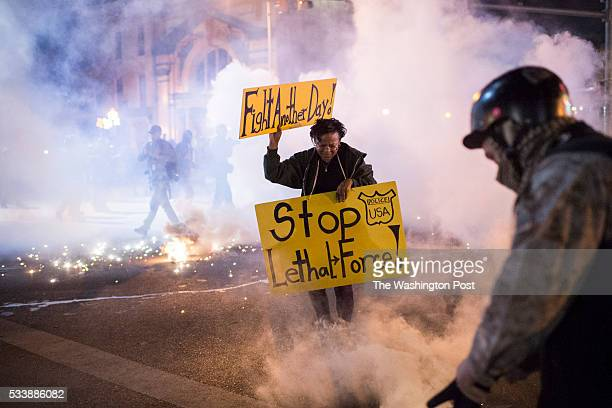 A woman runs with her signs as officers fire tear gas an d pepper balls as protestors walk for Freddie Gray on West North Avenue and protest around...