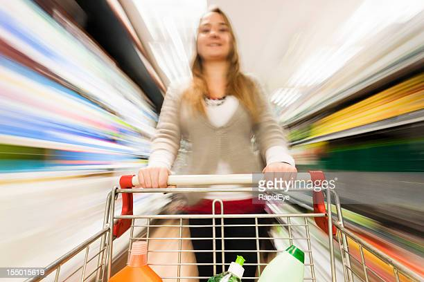 Woman rushes shopping trolley through supermarket with multicolored motion blur