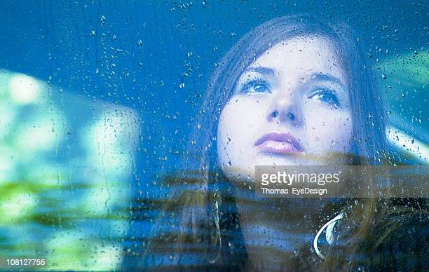 Woman Sadly Looking Through a Window in the Rain