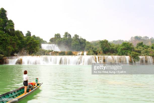 woman sailing in lake against waterfall - ko ko htike aung stock pictures, royalty-free photos & images