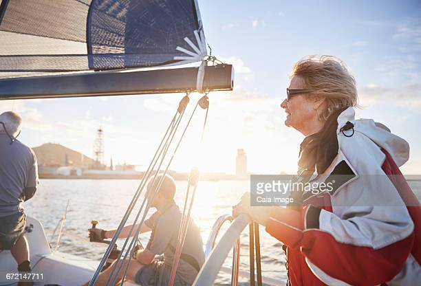 Woman sailing steering sailboat at helm on sunny ocean
