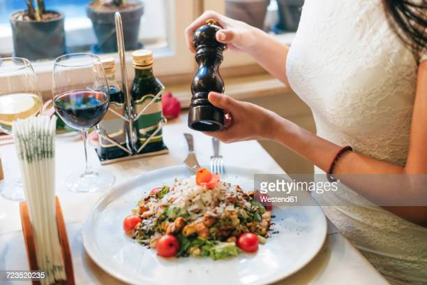 Woman salting her dinner, partial view