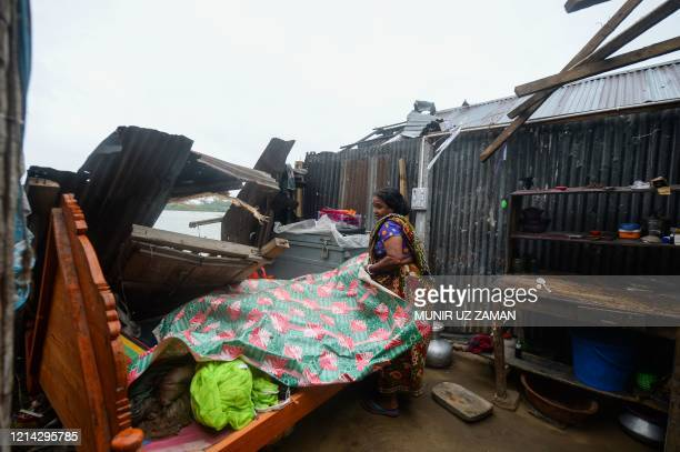 A woman salvages items from her house damaged by cyclone Amphan in Satkhira on May 21 2020 The strongest cyclone in decades slammed into Bangladesh...