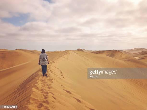 duna de areia da mulher que caminha à infinidade - deserto da namíbia - fotografias e filmes do acervo