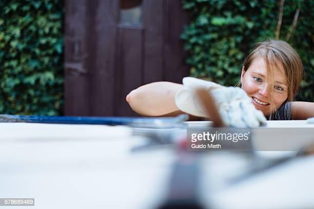 Woman sanding a wood board.