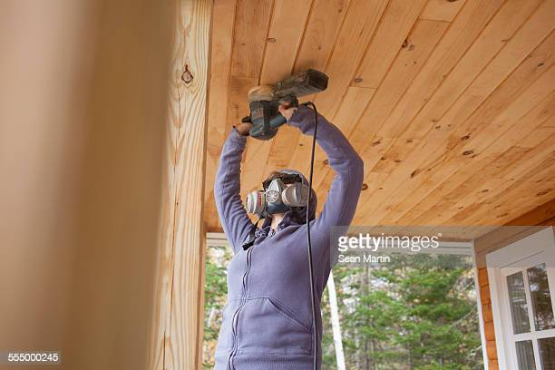 Woman sanding wooden ceiling in house