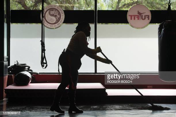 A woman sanitises the floor at the Chinese Martial Arts and Health Centre in Observatory as part of the COVID19 mitigating procedures in Athlone Cape...