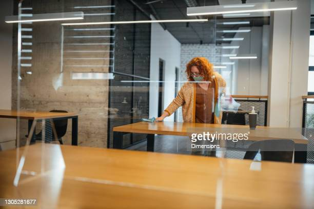 woman sanitizes table at work with disinfecting utility - antiseptic wipe stock pictures, royalty-free photos & images
