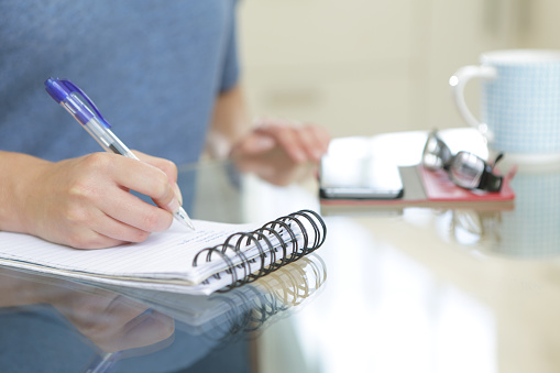 woman sat at table writing list - gettyimageskorea