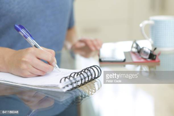 woman sat at table writing list