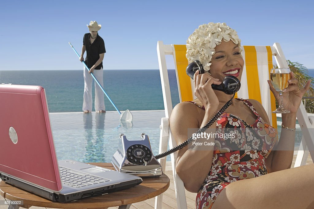 Woman sat by pool on phone : Stock Photo