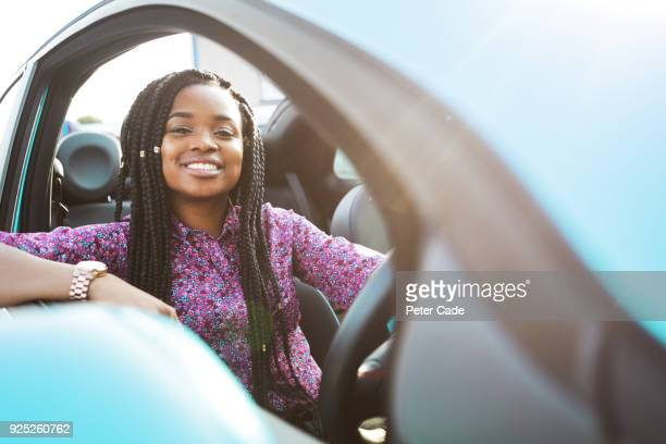 woman sat in blue car looking out of window - driver stock pictures, royalty-free photos & images