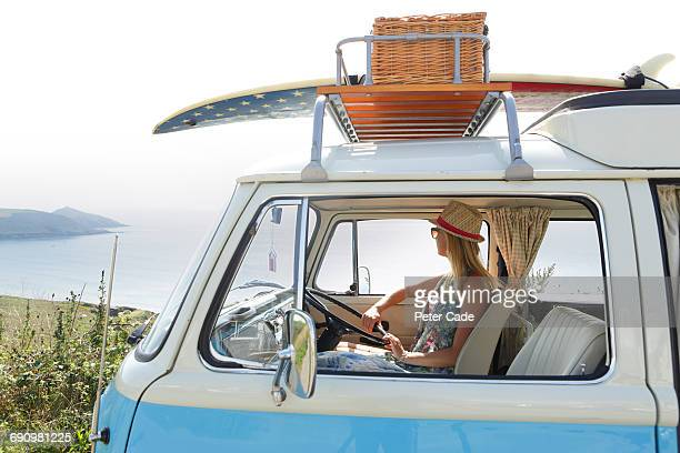 woman sat in camper on coastal road - camper van stock pictures, royalty-free photos & images