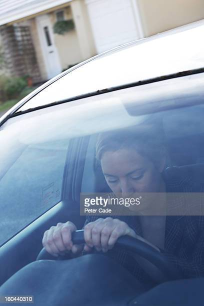 Woman sat in car outside house looking unhappy