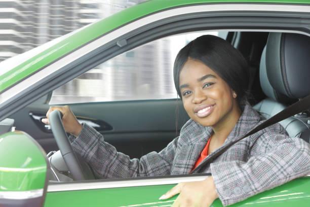 Woman sat in green car in city