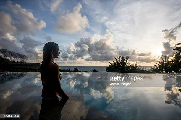 Woman sat in infinity pool with cloud reflections