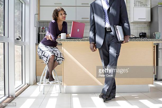 Woman sat in kitchen, man leaving for work