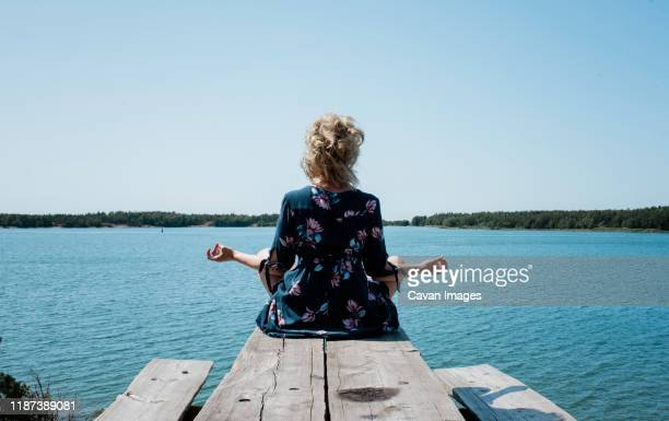 woman sat meditating outside looking at the sea on holiday - hot women on boats stock pictures, royalty-free photos & images