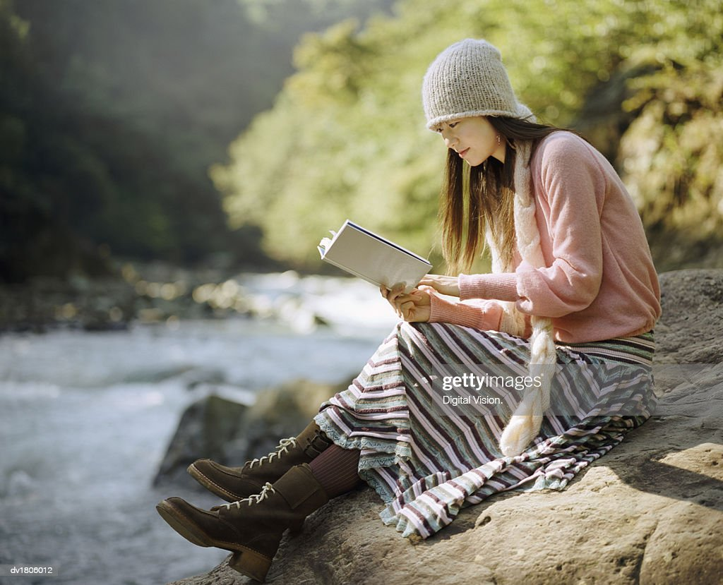 Woman Sat on a Boulder by a River, Reading a Book : Stock Photo