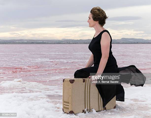 Woman sat on a suitcase in the shore of a lake