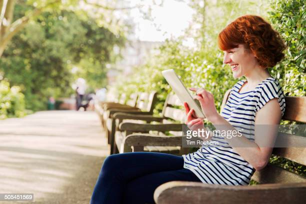 Woman sat on bench and using digital tablet.