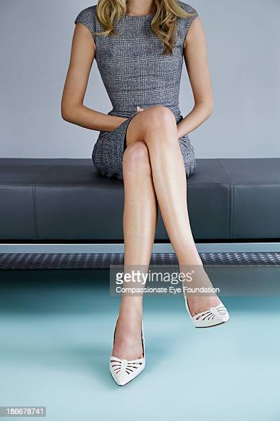 Woman sat on bench, legs crossed