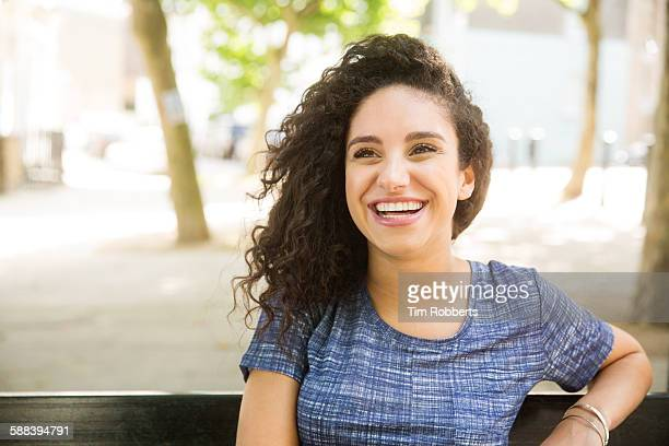 woman sat on bench smiling. - toothy smile stock pictures, royalty-free photos & images