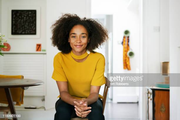woman sat on chair looking at camera - afro frisur stock-fotos und bilder