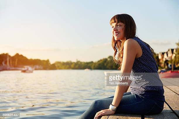 Woman sat on river jetty.