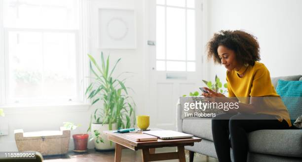 woman sat on sofa using smart phone - domestic life stock pictures, royalty-free photos & images