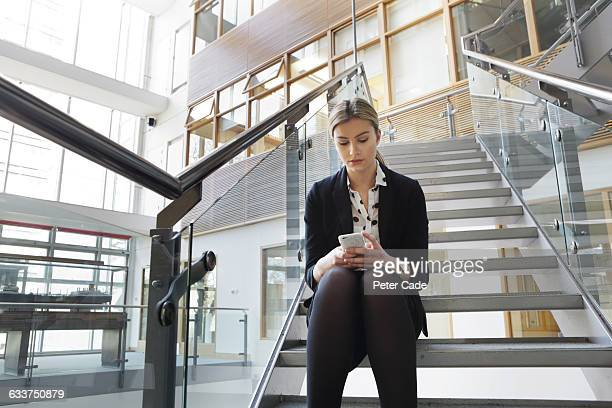 woman sat on stairs in office looking at phone - stocking tops stock photos and pictures