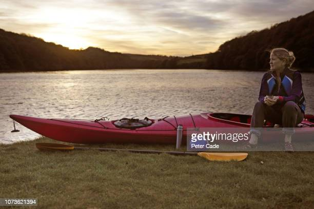 woman sat with kayak next to river - sea kayaking stock pictures, royalty-free photos & images
