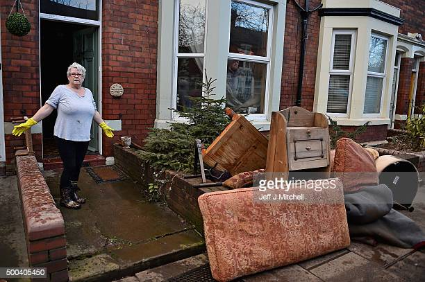 A woman satnds outside her home in Warwick road start to empty their possessions after Storm Desmond caused flooding on December 8 2015 in Carlisle...