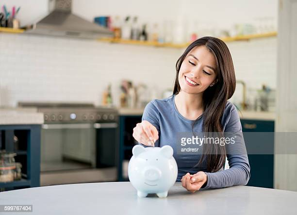 woman saving money in a piggybank - savings stock pictures, royalty-free photos & images