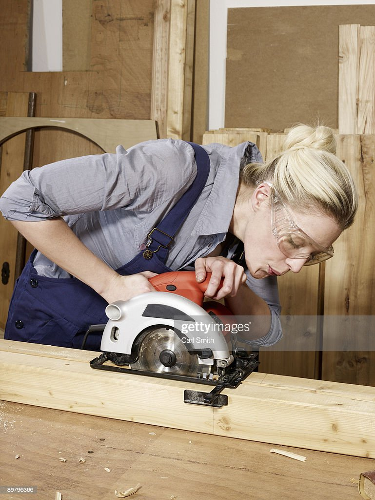 A woman sawing wood : Stock Photo