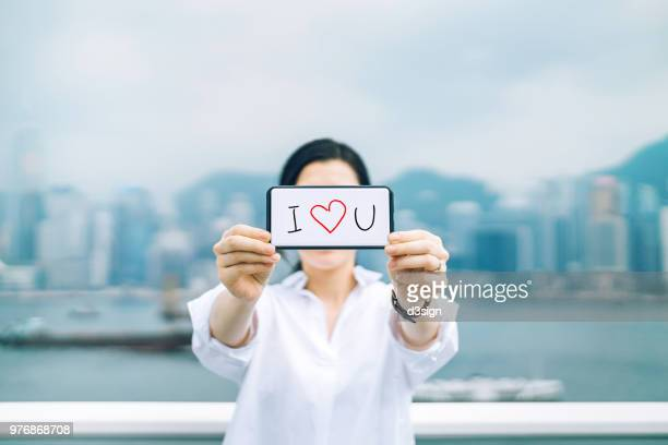 "woman saying ""i love you"" with smartphone in front of city skyline in the day - i love you stock pictures, royalty-free photos & images"
