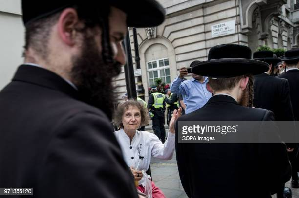 A woman saying 'shame on you' to the Orthodox Jews supporters of Palestine Hundreds of antiIsrael protesters marched through the streets on the...