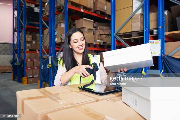 woman scanning boxes in storage room - femalefocuscollection stock pictures, royalty-free photos & images