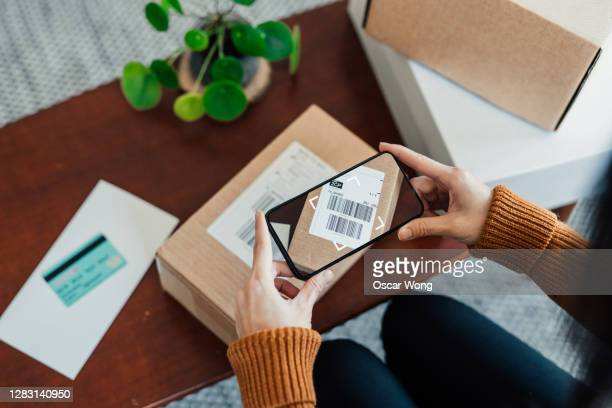 woman scanning delivery barcode on package with smart phone - cardboard box stock pictures, royalty-free photos & images