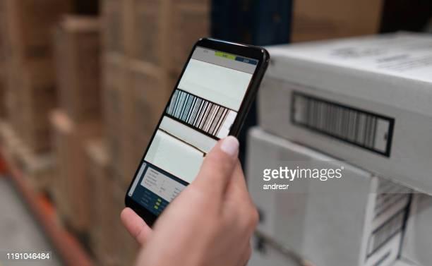 frau scannt produkte in einem lager mit einem mobiltelefon - strichkodeleser stock-fotos und bilder