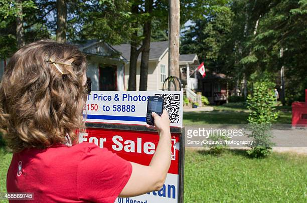 woman scanning qr code on for sale sign - security code stock photos and pictures