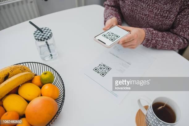frau, scannen den qr-code auf einer rechnung mit einem smartphone in der küche - strichkodeleser stock-fotos und bilder