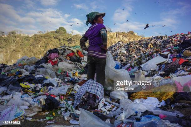 A woman scavenges for food clothes and other items in a landfill which is prone to fires and other accidents January 18 2014 in Guatemala City...