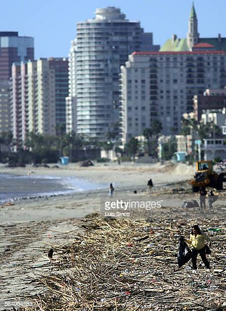Woman scavenges for recyclable materials amid the trash and debris delivered by storm drains and the Los Angeles River to the shoreline near downtown...