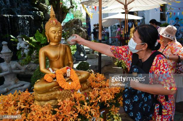 Woman scented water on a Buddha statue as they celebrate Songkran, also known as the Thai New Year, at Wat Pho temple in Bangkok, Thailand, 13 April...