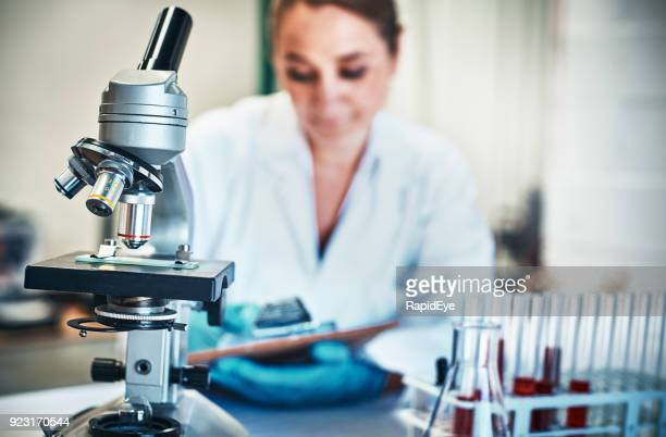 woman scientist at work, microscope and test tubes in foreground - microbiologist stock pictures, royalty-free photos & images