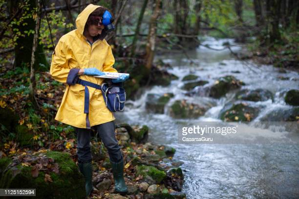 woman scientist ecologist taking samples of the soil and groundwater - ecologist stock pictures, royalty-free photos & images