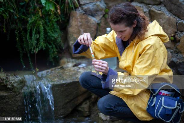 woman scientist ecologist taking samples of the spring water - ecologist stock pictures, royalty-free photos & images