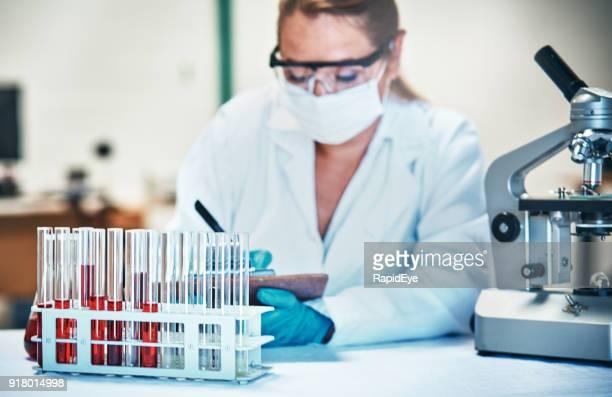 研究室で働いて防護服の女性科学者