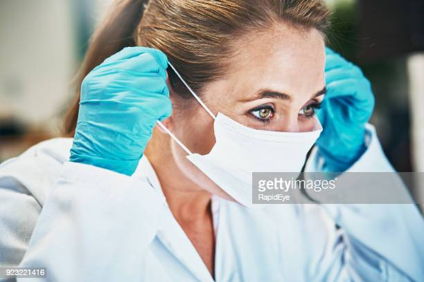 woman scientist or medical professional putting on mask - infectious disease stock pictures, royalty-free photos & images
